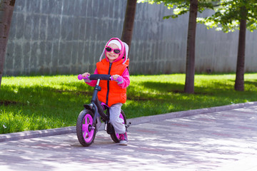 Active blond kid driving run bike the street alley of the city. Funny casual clothing vest jacket, sunglass and hood with bunny ears. Balance bike concept.