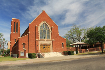 Red brick exterior of Grace Evangelical Lutheran Church in Tucson, Arizona with blue sky copy space,  stained glass windows and bell tower.