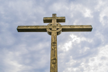 A wooden cross on top of a hill. Orthodox white cross glows on the top of the hill on the background of blue sky