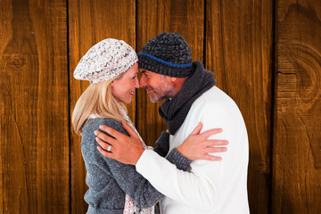 Happy couple in winter fashion embracing against overhead of wooden planks