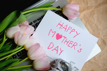 Bouquet of pink tulips and gift card on laptop, Happy mother's day.