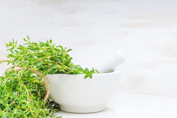 Thyme twigs in the pounder on white wooden table