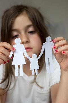 Little girl holds paper chain family; broken family or divorce concept
