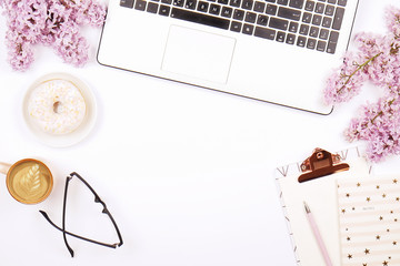 Feminine desktop, close up of laptop keyboard, blank clipboard, coffee & donut, lilac flowers. Flat lay composition, notebook computer, cappuccino cup, glasses eye wear, white background. Copy space.