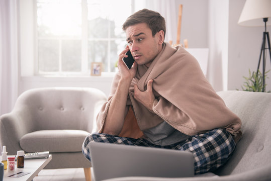 I am sick. Sad young man talking on the phone to his employer while asking about the sick leave
