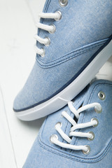 Fashionable shoes on a light wooden background, white shoelaces close-up.