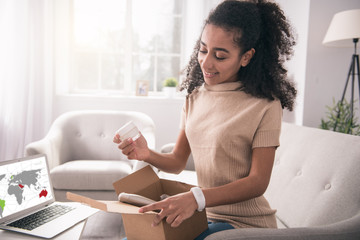Internet order. Joyful positive woman opening the box while looking at her order