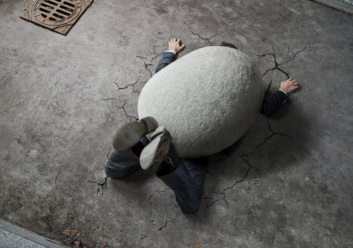 High angle view of businessman crushed by the huge stone on the street with copy space