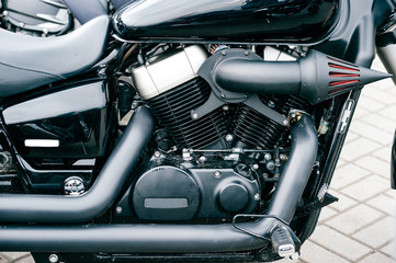 Closeup of motorbike with lots of chrome details. Modern powerful perfomance road motorcycle shiny reflexive surface engine with exhaust pipes. Vehicle industry. Two-wheeled vehicle technologies.
