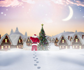 Santa walking in the snow against cute christmas village with tree