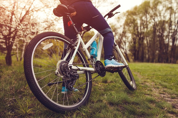 Young woman riding a bicycle in spring forest. Helathy lifestyle concept. Close-up of bike wheel