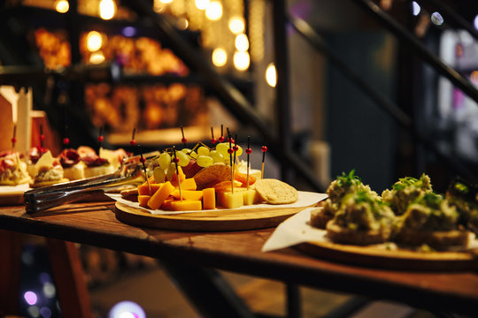 Snacks on a wooden shelf. Different cheese on a plate, grapes. In the background light bulbs. Yellow light. Snacks at the party