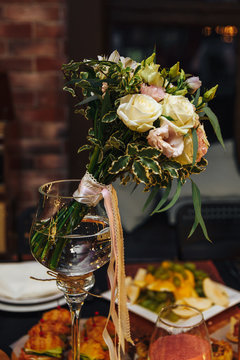 Wedding bouquet stands in a tall glass vase. In a bouquet of white roses, greenery, ribbons. Close up