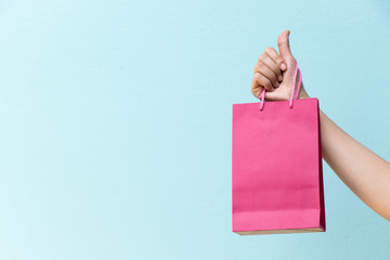 Hand of business woman hold pink shopping bag on blue concrete background