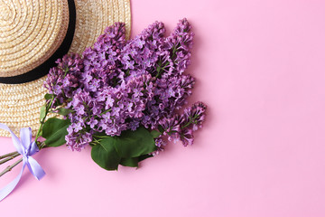 lilac and straw hat on a colored background with place for inserting text. minimalism, design, top view. flatlay