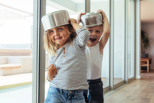 Kids playing knight with kitchen utensil at home