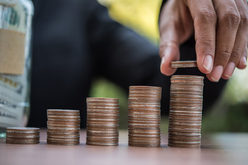 hand putting money coin stack growing business