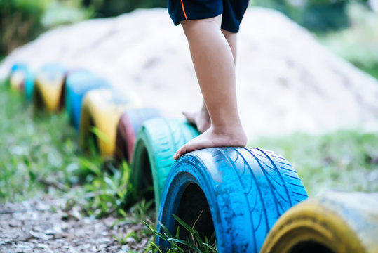 Kids  running on tires in the playground.