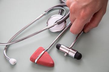 Neurologin nimmt Reflexhammer, Perkussionshammer und Stethoskop zur Diagnose