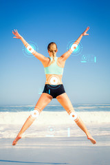 Fit woman jumping on the beach with arms out against fitness interface