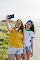Cheerful girls taking selfie outside