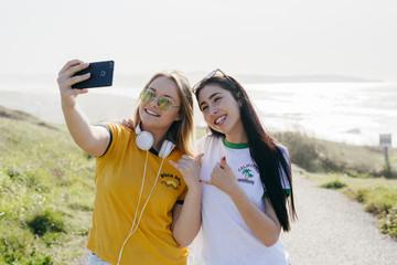 Cheerful girls taking selfie outside