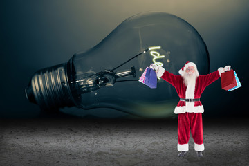 Santa carrying gifts against idea filament in light bulb