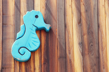 vacation and summer image with seahorse over wooden background.
