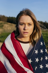 Portrait of young woman wrapped in American flag standing in a field