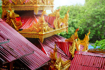 Architectural detail of colorful red and gold roofs on a temple in Mandalay