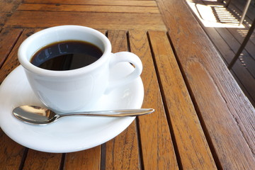 カフェのテラス席のコーヒー - A cup of coffee on the table at the outdoor wooden terrace