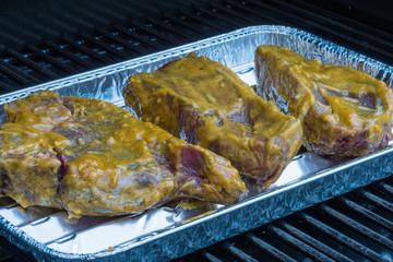 Frisch marinierte Steaks in einer Alu-Grillschale auf dem Grillfest