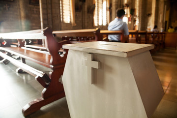 White donation box with a cross on it at a Christian church.  Collection box for generous offertory standing among pews at a Catholic temple