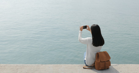 Woman taking the photo on cellphone with seascape