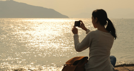 Woman taking photo with the sea under sunset