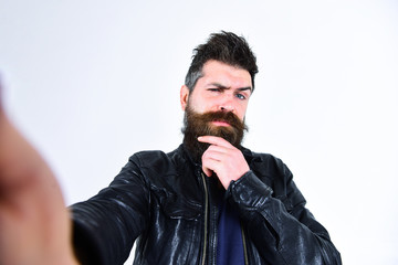 Man with beard and mustache on strict face looking at camera. Macho wears leather jacket, white background. Masculinity concept. Hipster looks serious and thoughtful while taking selfie photo.