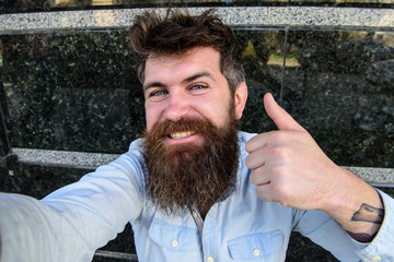 Hipster, tourist with tousled hair and long beard looking at camera, taking selfie photo. Selfie photo concept. Man, with beard on cheerful face shows thumb up gesture, black marble background.