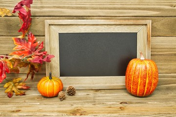 An empty chalkboard with a pumpkin and some other fall decorations.