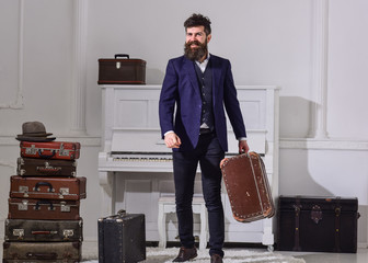 Man, traveller with beard and mustache with luggage, luxury white interior background. Baggage delivery concept. Macho elegant on smiling face stands near pile of vintage suitcase, holds suitcase.