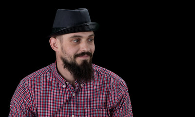 Pensive  bearded male dressed in a fleece shirt  and hat posing over black background
