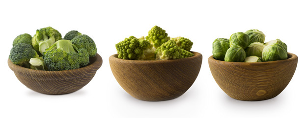 Different kinds of cabbage in a wooden bowl. Broccoli, Brussels sprouts, Roman cauliflower isolated on white background. Сabbage with copy space for text. Green food on a white background