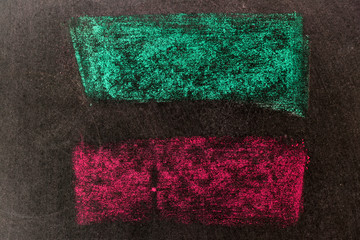 Green and red chalk drawing in line shape on black board background
