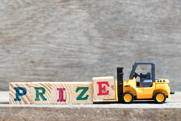 Toy forklift hold letter block e to complete word prize on wood background