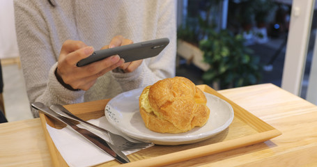 Woman taking photo on cellphone in coffee shop