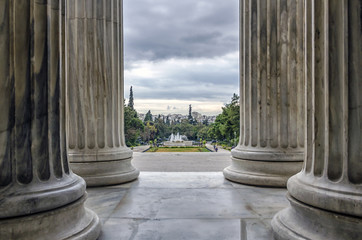 Zappeion, Athens - Greece. Looking through the columns of the Zappeion Megaron we see the park in front of it with the fountain and part of Athens city in the background