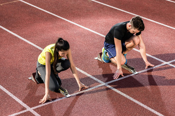 Male and female athlete in starting position at starting block of cinder track