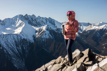 A girl is drinking tea on top of a mountain