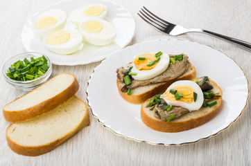 Sandwiches with canned sprats, chopped scallion and eggs in plate