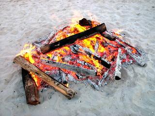 Wärmendes Lagerfeuer mit glühenden Holzscheiten am Strand von Binz auf Rügen an der Ostsee in Mecklenburg-Vorpommern