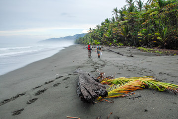 In the early morning, two hikers take the way to Corcovado on the black sand beach of the Osa peninsula in Costa Rica. Fototapete